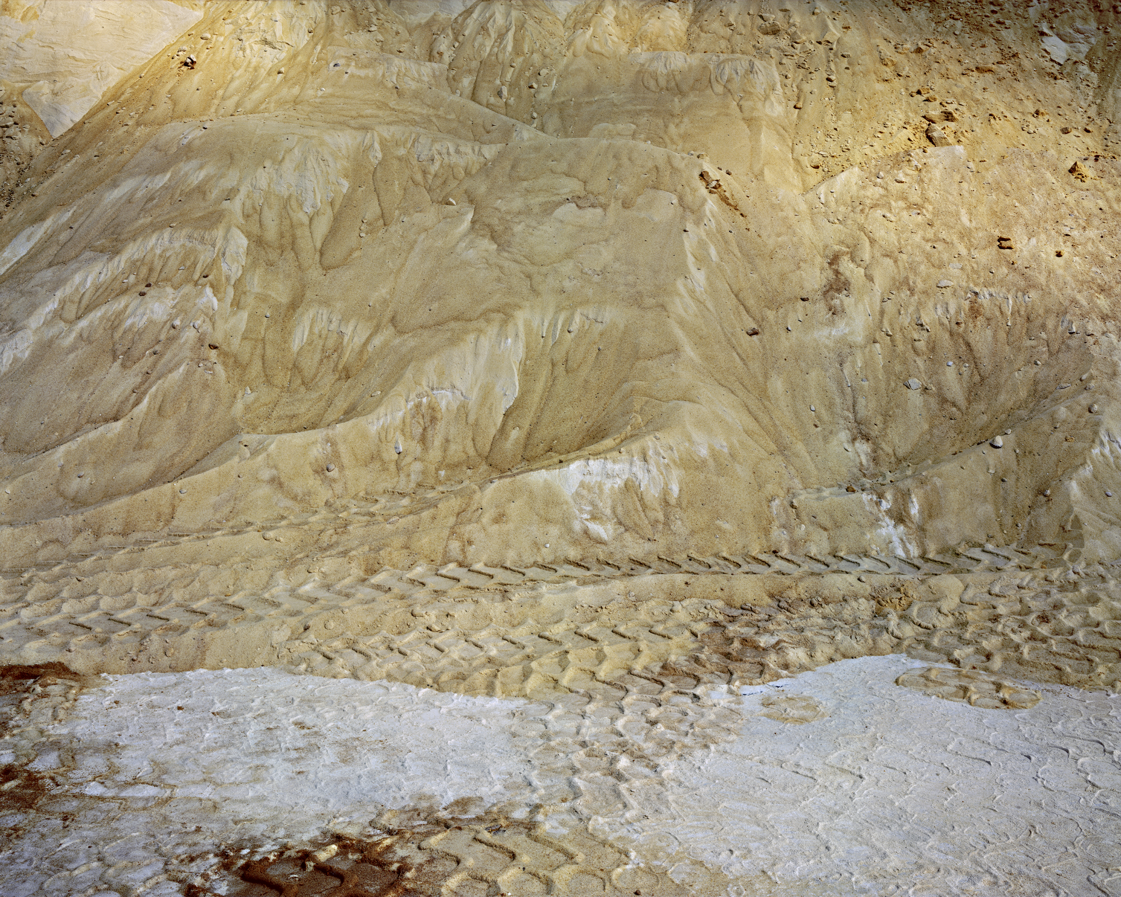 Sugar mounds in a warehouse with vehicle tracks on it combining to form a scale like pattern